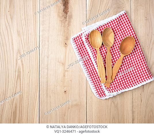 three empty wooden spoons on a red kitchen towel, copy space