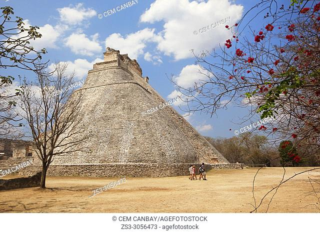 Tourists in front of the Pyramid of the Magician in prehispanic Mayan city of Uxmal Archaeological Site, Yucatan Province, Mexico, Central America