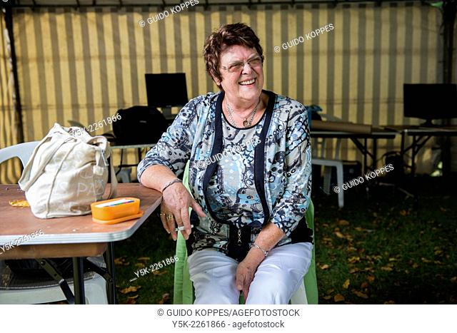 Tilburg, Netherlands. Laughing middle aged woman with handbag and box of cigarettes sitting at a table