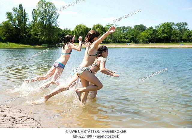 Group of girls splashing and playing in a lake