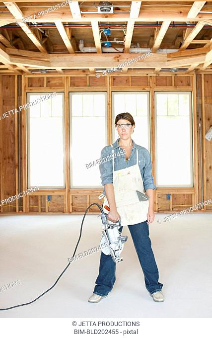 Caucasian construction worker standing in unfinished room with saw