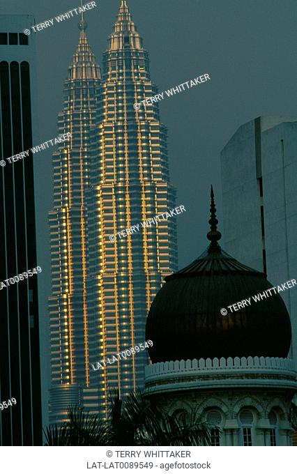 Petronas towers. Two tall pointed towers. Outlined in light. Grey sky. Mosque dome