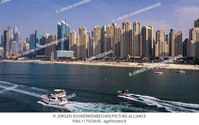 """The Beach"""""""" is the name of the popular beach section in Dubai, behind which the imposing skyscrapers of the exclusive Marina Bay district rise"""
