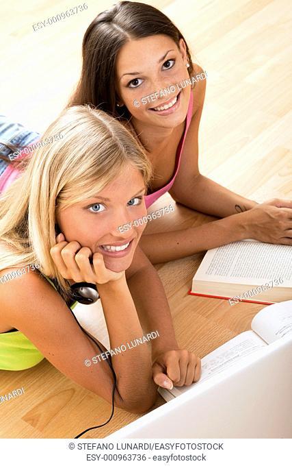 Happy teenage girls studying on the floor