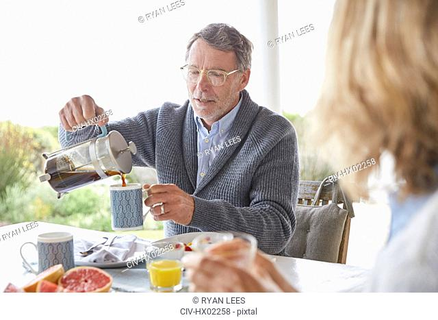 Senior man pouring coffee from French Press on patio