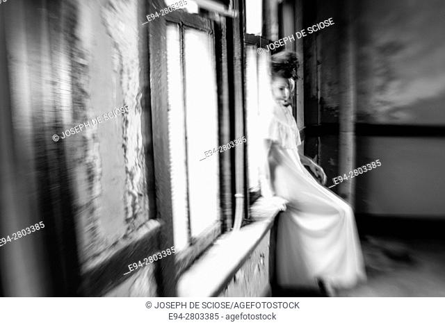 A 25 year old woman wearing a white dress looking away from the camera standing in an abandoned building, black and white