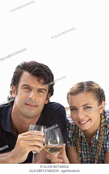 Couple toasting with wine at picnic