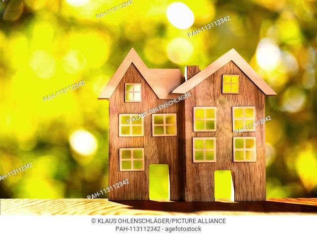 Two wooden houses on wooden floor in front of nature background with bokeh | usage worldwide