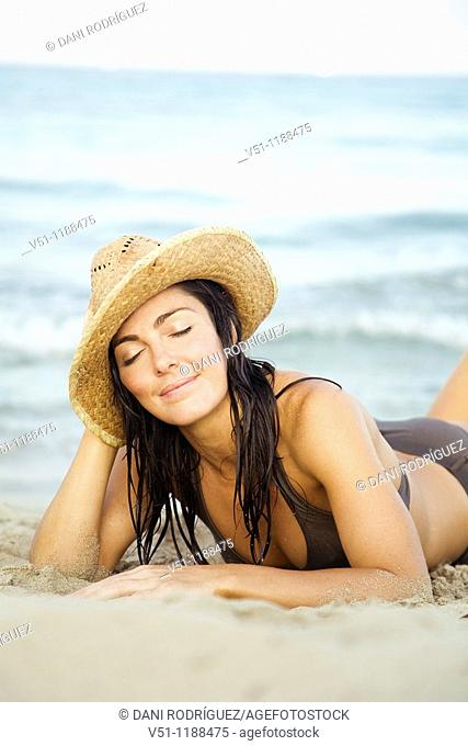 Portrait of a brunette woman laying on the beach in Ibiza, Balearic Islands