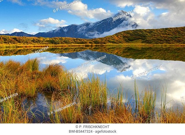 Piz Beverin mirroring in a mountain lake Pascuminersee, Switzerland, Grisons