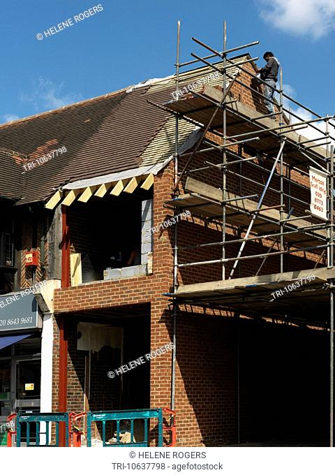 Man On Scaffolding Working On Construction Expansion Of A Shop With A Flat Above England