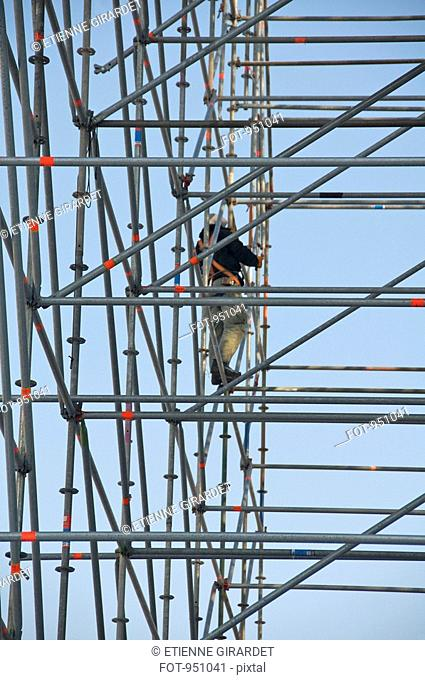 A construction worker standing on scaffolding