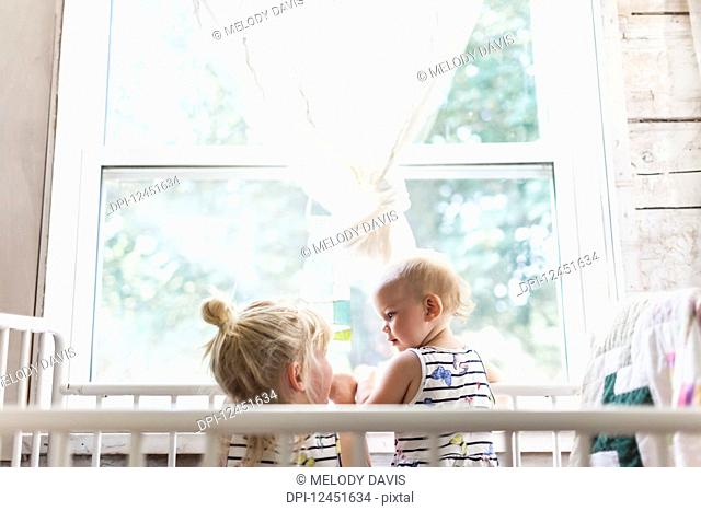 Two sisters, a baby and a toddler, play together in a crib by a window; Sorrento, British Columbia, Canada