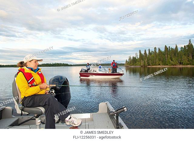 A woman in her boat and a family in another boat all fish on a lake in Northern Ontario; Ontario, Canada