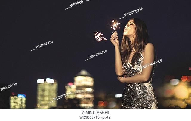 A young woman in a sequined dress dancing on a rooftop at night holding a party sparkler