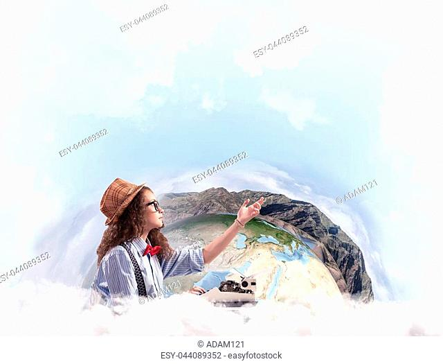 Beautiful woman writer in hat and eyeglasses pointing up while using typing machine at the table with Earth globe and cloudy skyscape on background
