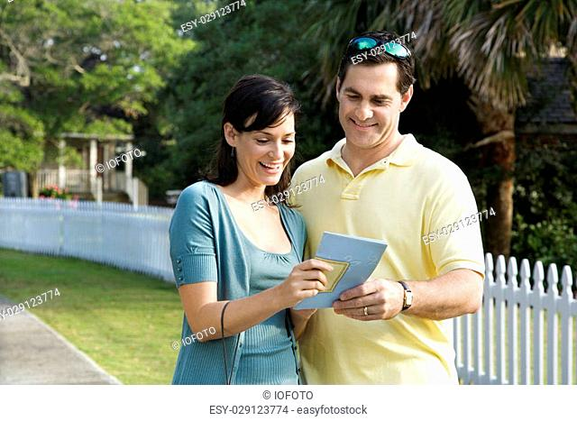 Mid-adult Caucasian couple holding a map and smiling