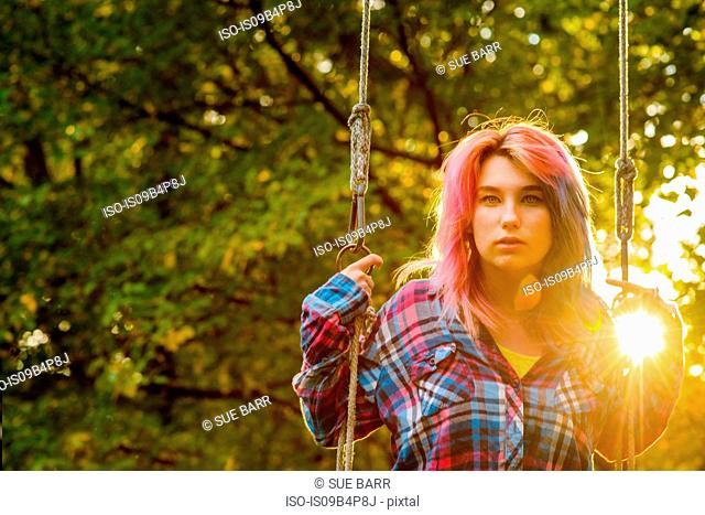 Portrait of teenage girl with multi-coloured hair, on garden swing