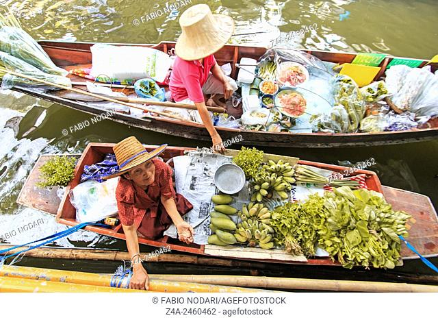 Bangkok, Thailand: Old woman selling fruits and vegetables in a traditional floating market