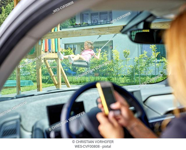 Girl on swing and woman in electric car texting on cell phone