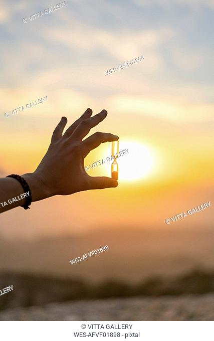Close-up of man's hand holding an hourglass at sunset