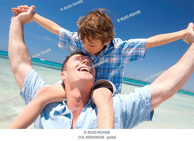 Boy getting shoulder carry from father on beach, Majorca, Spain
