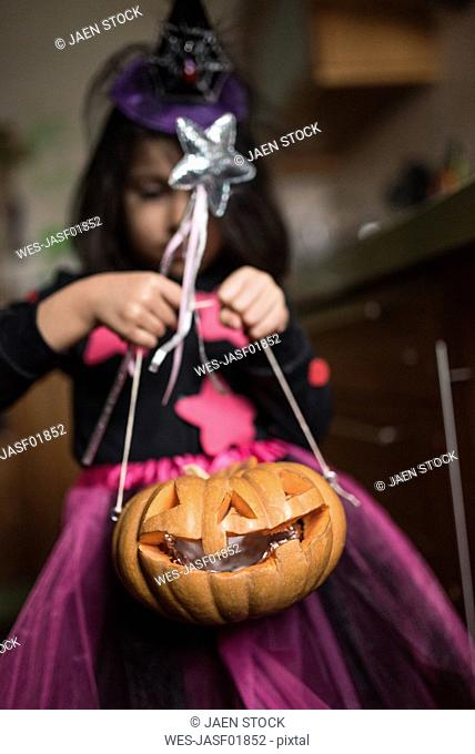 Little girl with Jack O'Lantern at Halloween