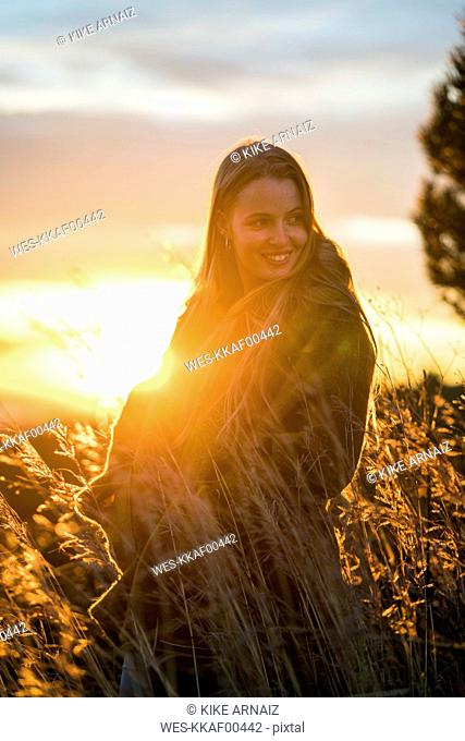 Smiling young woman in nature at sunset turning around