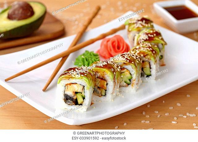 Green dragon sushi roll with eel, avocado, cucumber, wasabi and ginger. Traditional asian rice sushi healthy seafood. White plate, wooden table background