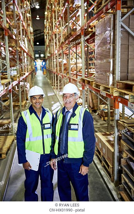 Portrait confident manager and worker in distribution warehouse aisle