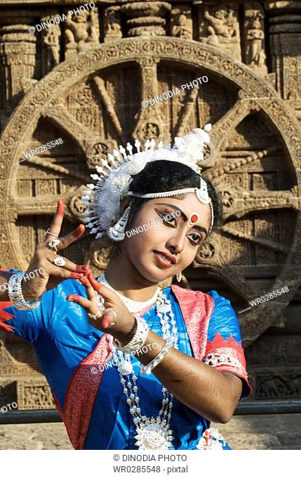 Odissi dancer strike pose re-enacts Indian myths such as Ramayana in front of iconic Sun Chariot in world heritage Sun temple complex in Konarak , Orissa