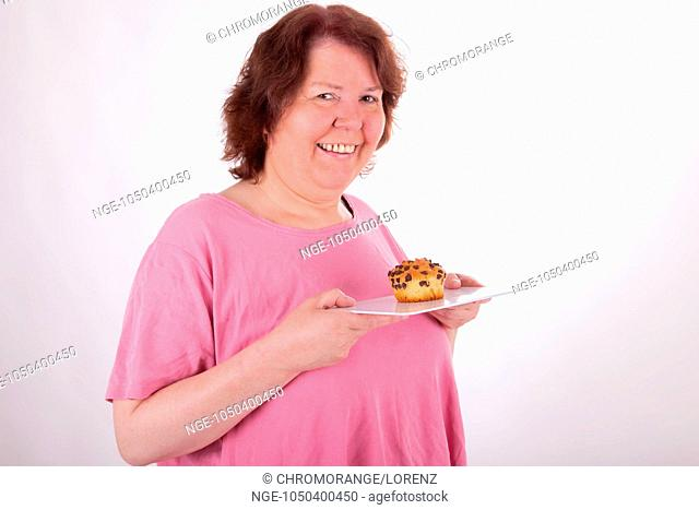 A fat woman with a muffin in her hand