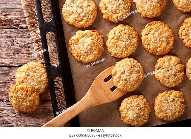 Anzac biscuits close up on a baking sheet on the table. horizontal view from above