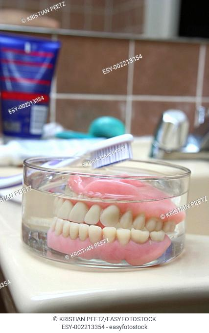 Kind of scary, isn't it :-    an artificial denture of a senior in a glass of water in the bathroom with the toothbrush aside  Shallow depth of field and focus...