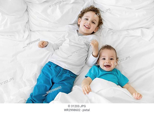 High angle view of boy wearing blue trousers and baby boy wearing blue T-shirt on a bed