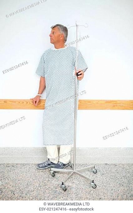 Man is standing against the wall of the corridor in the hospital with his IV dri