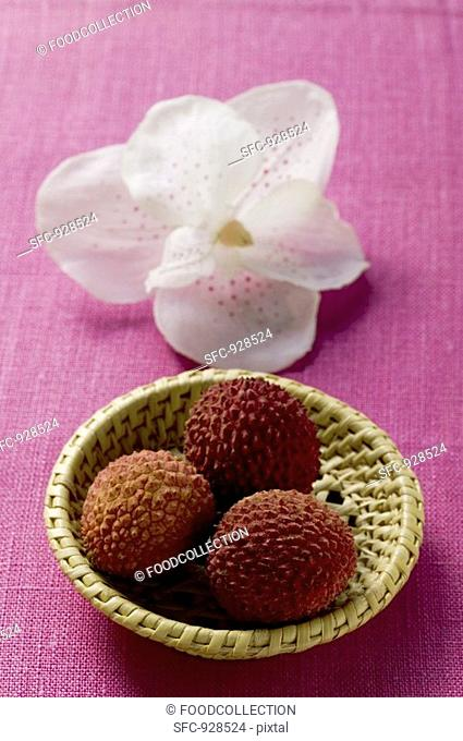 Lychees in basket in front of orchid