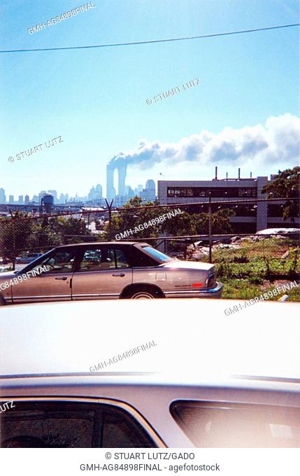 During the terrorist attacks of September 11, 2001, smoke is seen rising from the site of the World Trade Center, viewed over the roof of parked cars in Jersey...