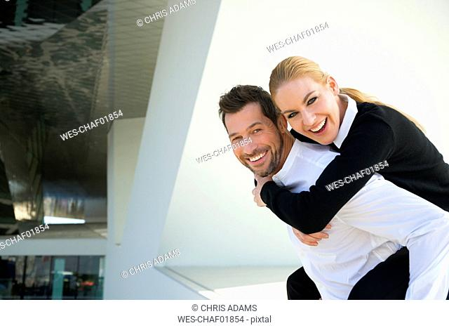 Portrait of happy businessman carrying woman piggyback