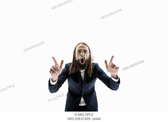 Portrait exuberant businessman with beard gesturing and yelling against white background