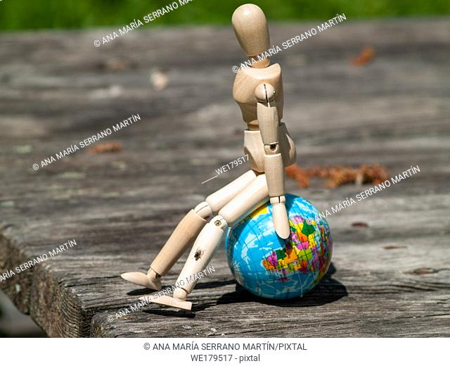 A wooden mannequin sitting on a world ball. Concept of ecology, globalization