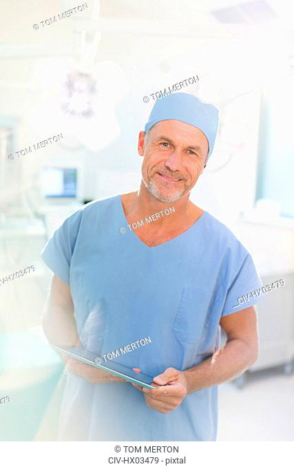 Portrait male surgeon using digital tablet in operating room