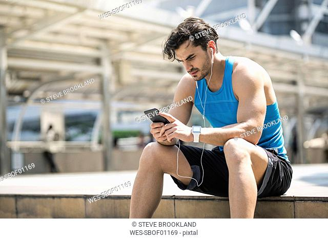 Runner wearing earphones, checking messages on his smartphone