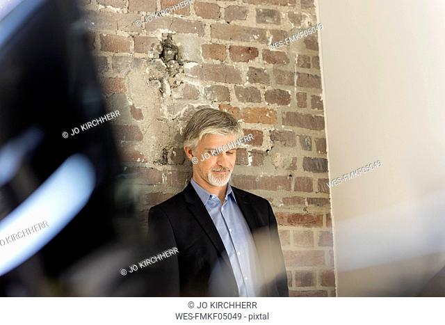 Mature businessman leaning on brick wall in office