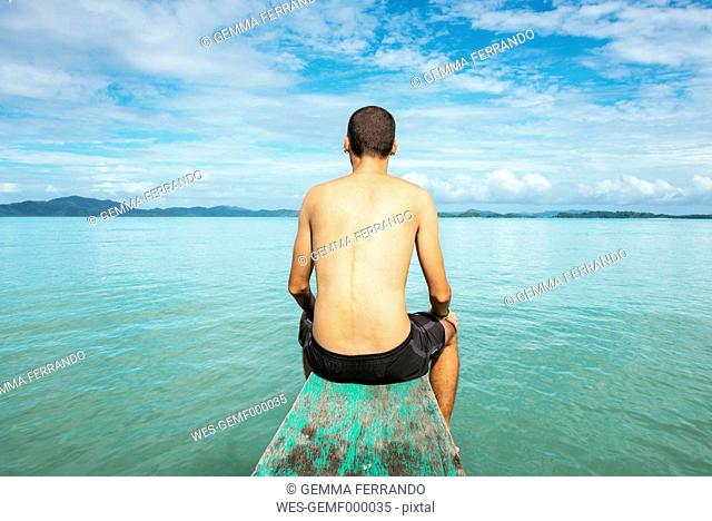 Philippines, Palawan, El Nido, man sitting on the bow of a boat