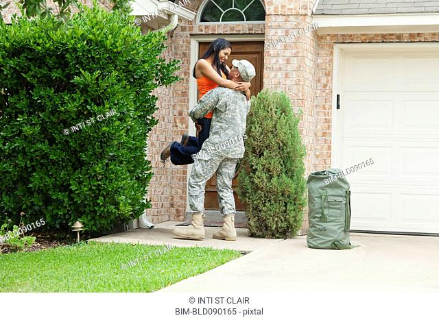Solder returning home greeting excited wife