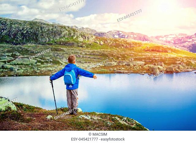 Best Norway hike. Back view of cute boy with hiking equipment in the mountains
