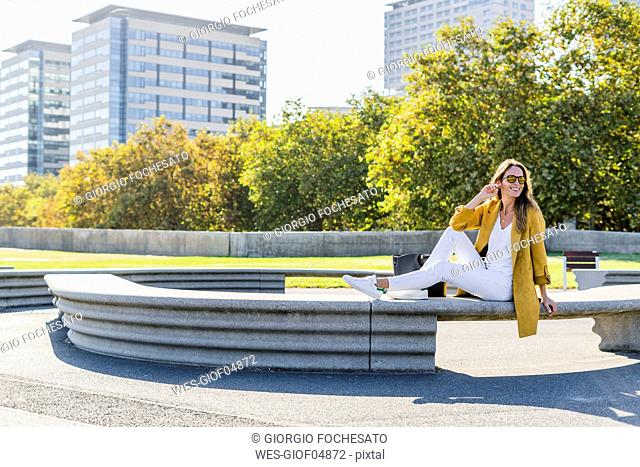 Happy woman sitting on a bench in the city