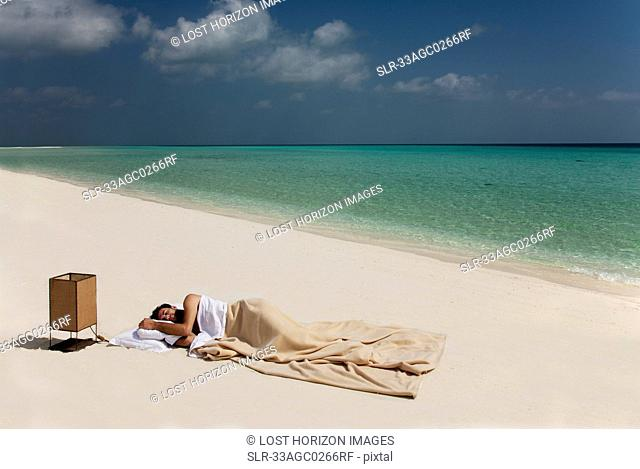 Man sleeping in bed on beach