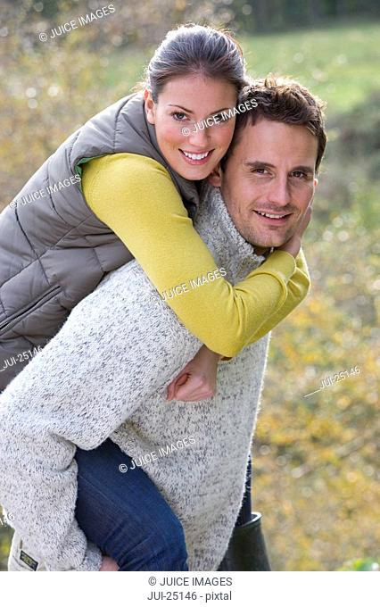 Smiling husband giving wife piggyback ride outdoors